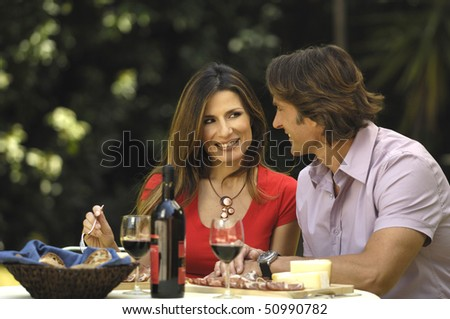 Man and woman eating in the garden - stock photo