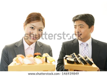 Man and woman eating sushi - stock photo