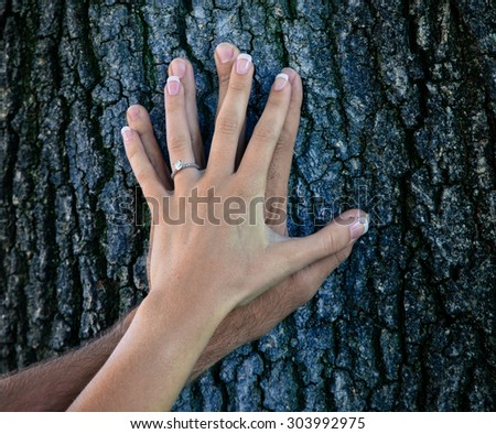 man and woman engagement ring showing off on tree trunk with instagram filter - stock photo
