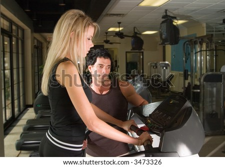 Man and woman exercising together at a fitness center on a treadmill walker exercise machine.  Man could be a personal fitness trainer. - stock photo