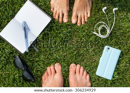 Man and woman feet and other stuff on the grass, planing a vacation - stock photo