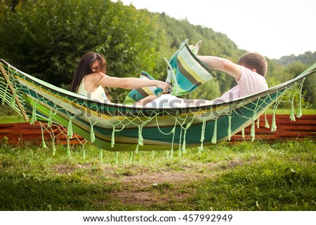 Man and woman fight towels lying on the hammock