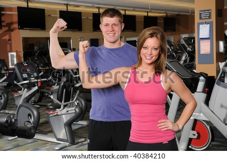 man and woman flexing arm at the gym