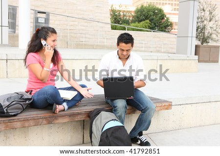 Man and woman friends at college campus studying with laptop computer - stock photo
