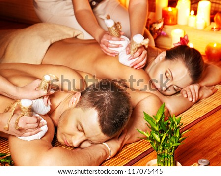 Man and woman getting herbal ball massage in bamboo spa. - stock photo