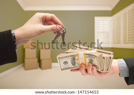 Man and Woman Handing Over Cash For House Keys Inside Empty Green Room with Boxes. - stock photo