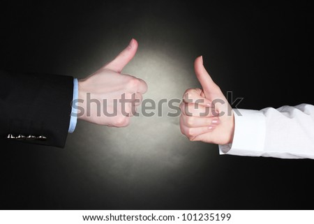man and woman hands with thumbs up ok signal on black background