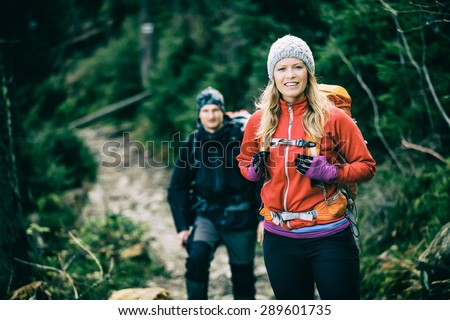 Man and woman happy couple hikers trekking in green autumn forest and mountains. Young people walking on trail with backpacks, healthy lifestyle adventure, camping on hiking trip, vintage photo style. - stock photo