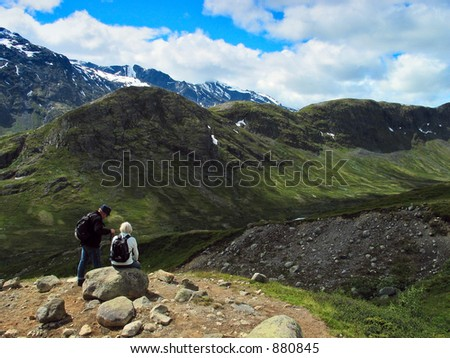 Man and woman have a rest among mountains. Jotunheimen national park, Norway - stock photo
