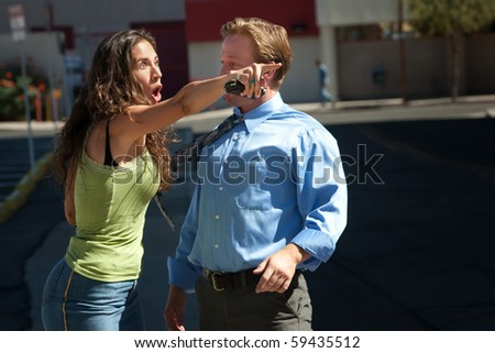 Man and woman have intense discussion on a city street.