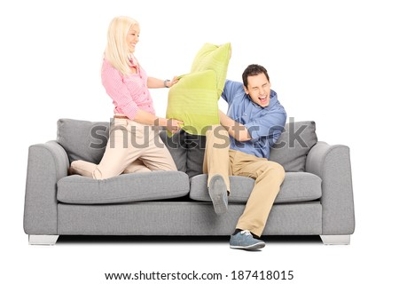 Man and woman having a pillow fight on couch isolated on white background - stock photo