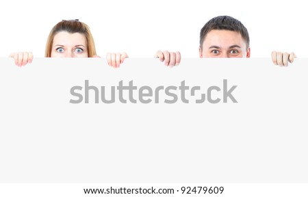 Man and woman hiding behind a copy space against a white background - stock photo