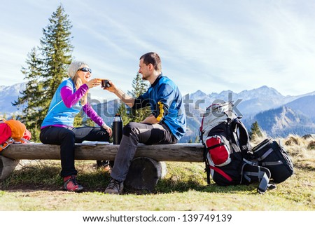 Man and woman, hikers camping in mountains. Young couple drinking and planning trip. - stock photo