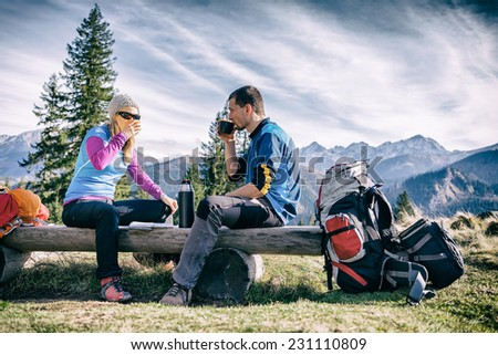 Man and woman hikers hiking and drinking in mountains. Young couple looking at map and planning trip or get lost. Vintage style trekking and recreation concept - stock photo