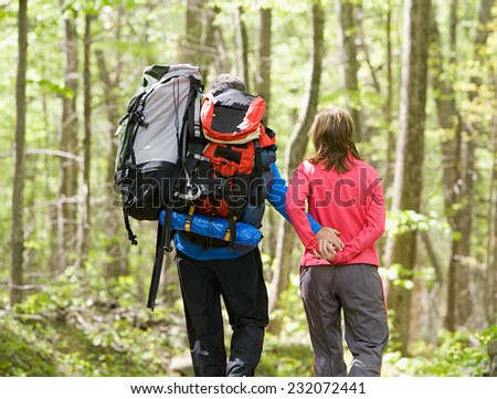 Man and woman hikers hiking on mountain - stock photo