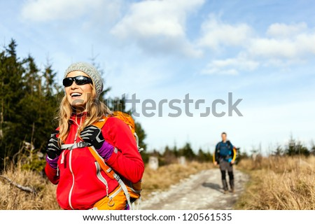 Man and woman hikers hiking on mountain trail autumn or winter nature. Young couple backpackers walking in forest, Poland. - stock photo