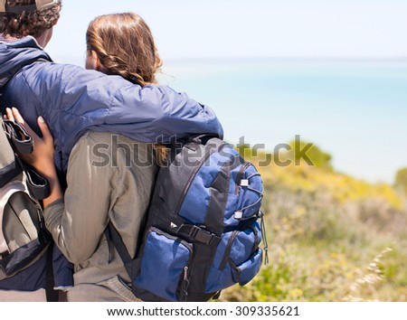 Man and woman hikers trekking in mountains - stock photo