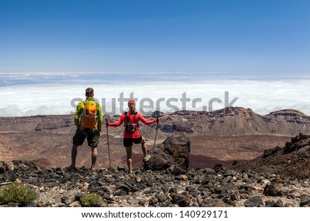 Man and woman hikers trekking in summer mountains. Young couple on rocky mountain range looking at beautiful view, Tenerife and El Teide on Canary Islands. Sport and exercising outdoors in nature.