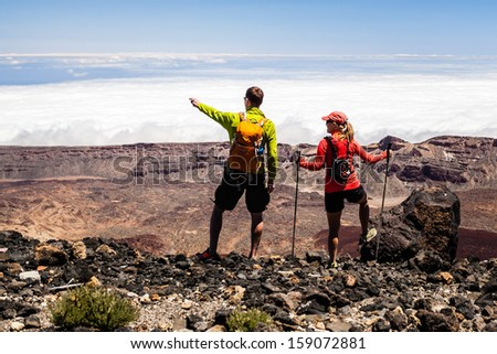 Man and woman hikers trekking in summer mountains. Young couple on rocky mountain ridge looking at beautiful view. Hiking on volcano mountain over clouds, Tenerife Canary Islands - stock photo