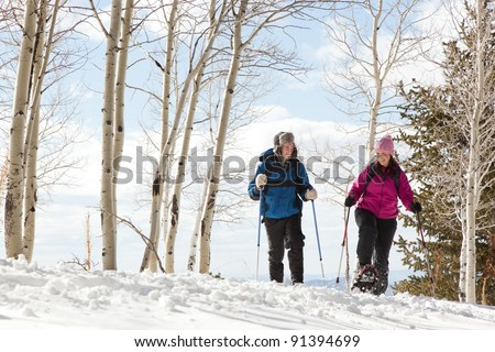 Man and Woman Hiking in Forest with Snowshoes - stock photo