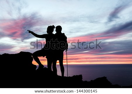 Man and woman hiking silhouette in mountains, sunset and ocean. Male and female couple hikers with walking sticks on top of mountain looking at beautiful night landscape, La Palma Canary Islands. - stock photo