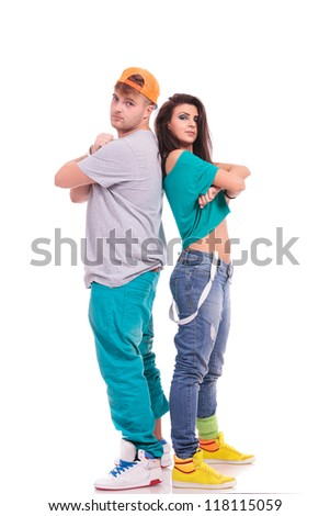 man and woman hip hop dancers standing back to back with arms folded and looking at the camera - stock photo