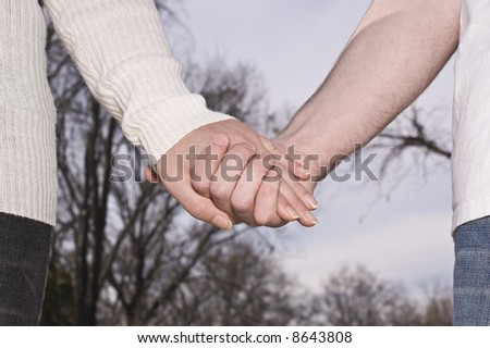 Man and woman hold hands as they walk