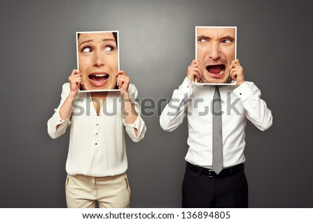 man and woman holding amazed shouting faces. concept photo over grey background - stock photo