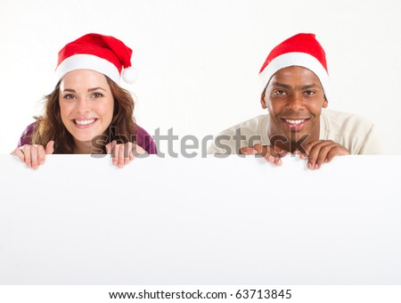 man and woman holding christmas banner - stock photo