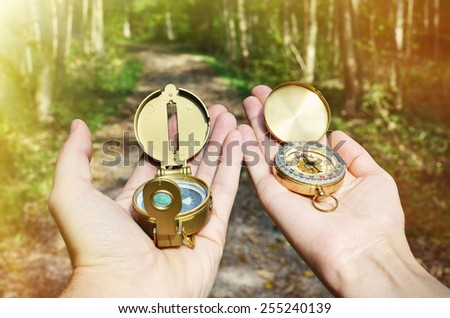 Man and woman holding compasses - stock photo