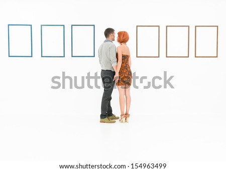 man and woman holding hands in front of empty frames displayed on white walls