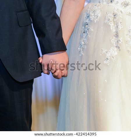 Man and woman holding hands in wedding celemony - stock photo