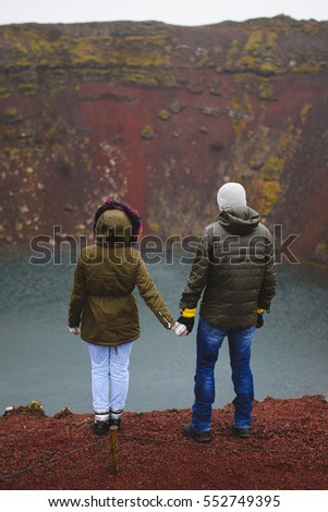 man and woman holding hands looking at Iceland lake