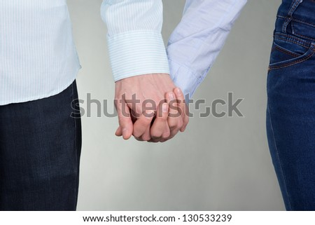 man and woman holding hands over grey background