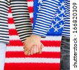Man and woman holding hands together against U.S. flag. Young couple wearing marine sailor uniform holding hands together - stock photo