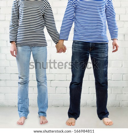 Man and woman holding hands together against white brick wall background. Young couple wearing marine sailor uniform holding hands illustrating love and friendship - stock photo