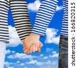 Man and woman holding hands together over blue sky background. Young couple wearing marine sailor uniform holding hands illustrating love and friendship - stock photo