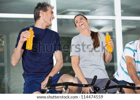Man and woman holding juice bottles while laughing in health club - stock photo