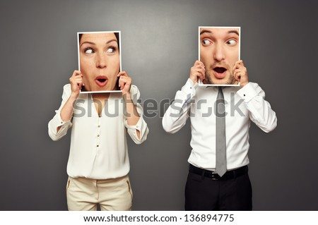 man and woman holding surprised faces. concept photo over grey background - stock photo