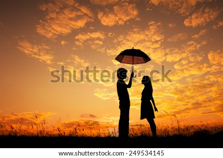 Man and woman holding umbrella in evening sunset silhouette - stock photo