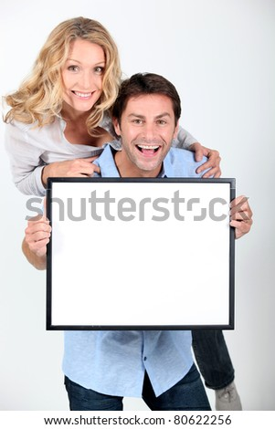 Man and woman holding up a blank poster - stock photo