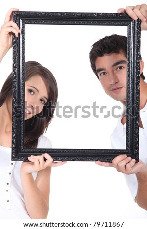 Man and woman holding up a picture frame - stock photo