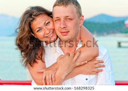 man and woman hugging near the sea