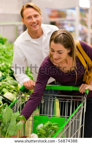Man and woman in a supermarket at the vegetable shelf shopping for groceries, she is putting some stuff into the shopping cart - stock photo