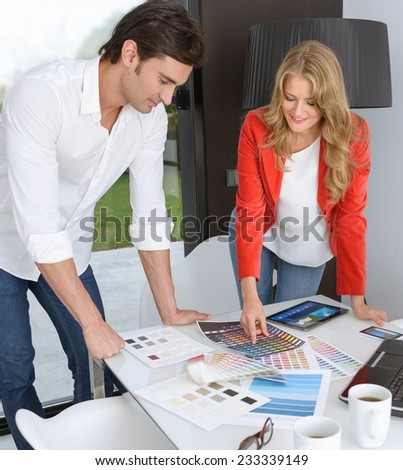Man and woman in an office surrounded by color charts, material samples and technology - stock photo