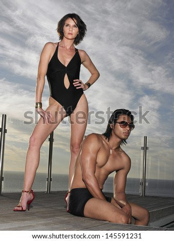 Man and woman in bathing suits on pool deck near ocean - stock photo