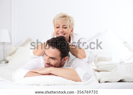 Man and woman in bed. Fun, frolic a mature couple. Showing love by mature person. Pleasant morning a couple of lovers.