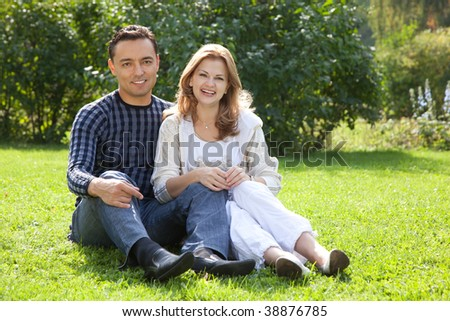 man and woman in braces laughing outdoors - stock photo