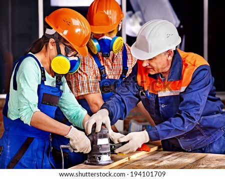 Man and woman in builder helmet with electric planer. - stock photo