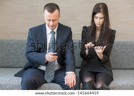 Man and woman in business suits sitting on the couch with a communication device, focus on a man.